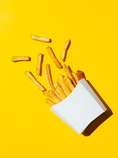 Spilled white box of french fries Free Photo