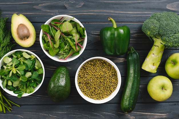 Spinach; avocado; bell pepper; broccoli; apple; cucumber on wooden desk Free Photo