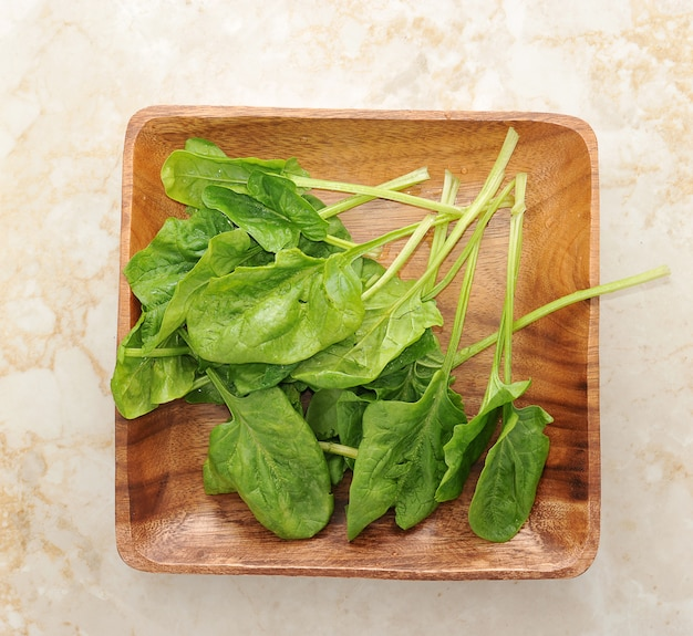 Spinach leaves in a wooden bowl Premium Photo