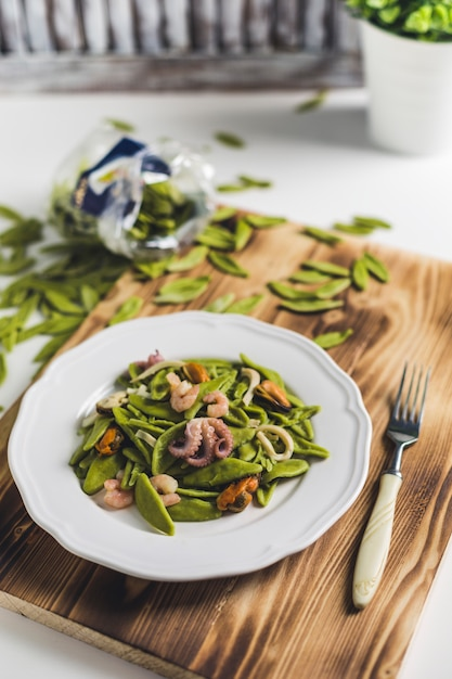 Spinach pasta with seafood on a white plate on a wooden board Premium Photo