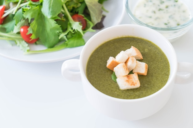 Spinach soup with spinach leaves and bread Free Photo