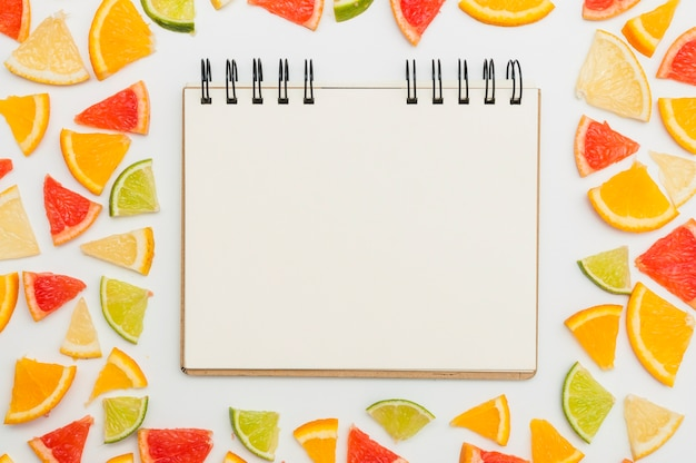 Spiral blank notepad surrounded with citrus triangular slices on white background Free Photo