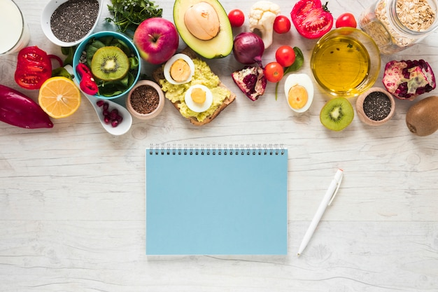 Spiral book; pen; fresh fruits; toasted bread; vegetables and ingredients on white textured background Free Photo