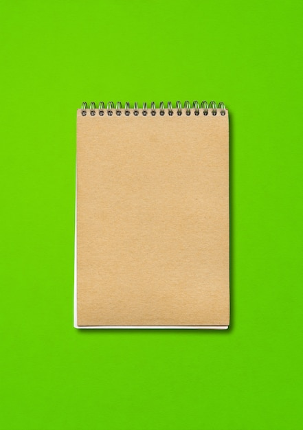 Spiral closed notebook mockup, brown paper cover, isolated on green background Premium Photo