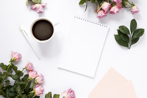 Spiral notepad; black tea; pen and flowers on white backdrop Free Photo