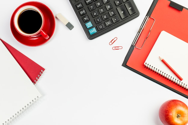 Spiral notepad,coffee cup,eraser,calculator,spiral notepad on clipboard with red whole apple on white background Free Photo