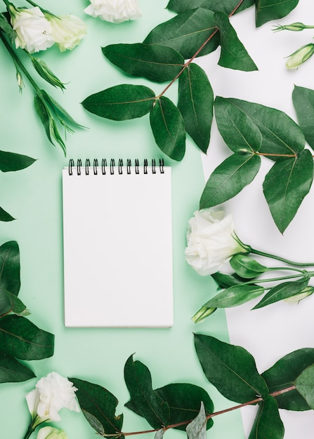 Spiral notepad eustoma flowers and leaves on dual green and white background Free Photo