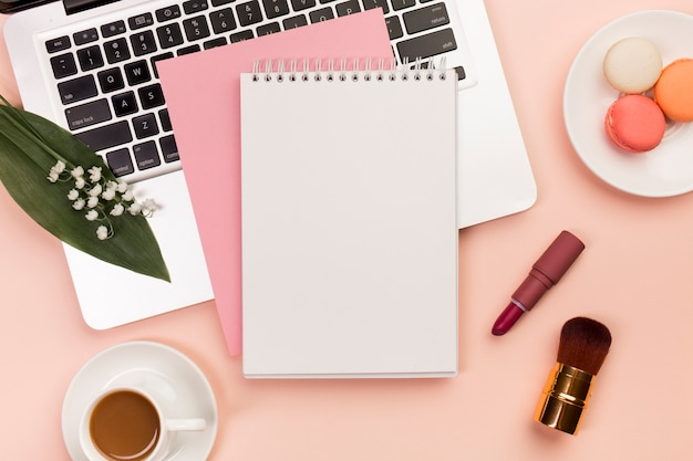 Spiral notepad on laptop with macaroons and coffee cup with makeup brushes on colored backdrop Free Photo