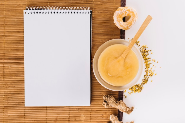 Spiral notepad; lemon curd; bee pollen; donut and ginger on placemat Free Photo