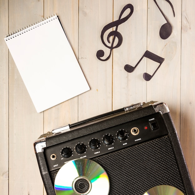 Spiral notepad; musical note and amplifier with compact disc on wooden desk Free Photo