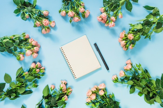 Spiral notepad and pen surrounded with fresh roses flowers on blue background Free Photo
