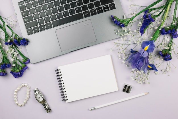 Spiral notepad; pencil; wristwatch; bracelet and purple flowers with laptop on white background Free Photo
