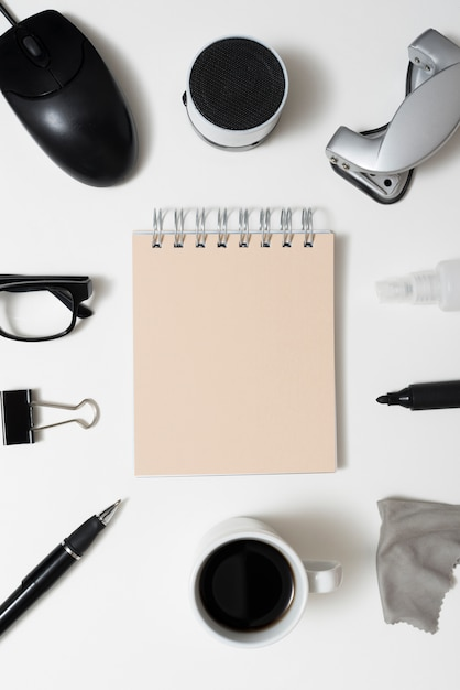 Spiral notepad surrounded by office stationery; coffee cup and eyeglass over isolated on white background Free Photo