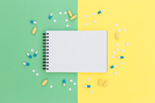 Spiral notepad surrounded with pills on green and yellow background Free Photo