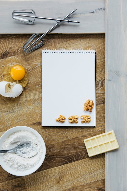 Spiral notepad; walnut; chocolate; flour; egg and whisk on wooden surface Free Photo