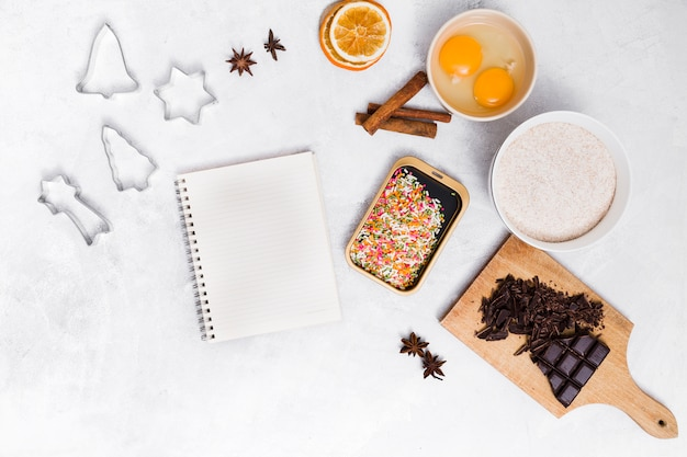 Spiral notepad with colorful sprinkles; pastry cutter; star anise; cinnamon; dried citrus; egg yolk and chocolate bar on white backdrop Free Photo