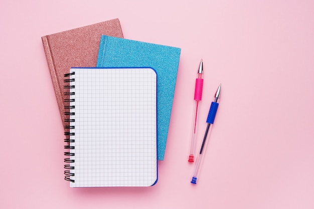 Spiral notepad with pens as mockup for your design on pink. back to school concept. copy space, top view. Premium Photo