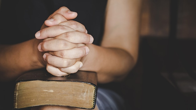 Spirituality and religion, hands folded in prayer on a holy bible in church Free Photo