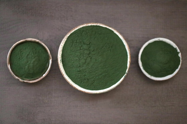Spirulina algae. dry powder in round cups set on a black table. Premium Photo