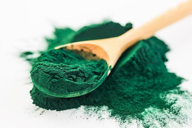 Spirulina powder in a wooden spoon Premium Photo