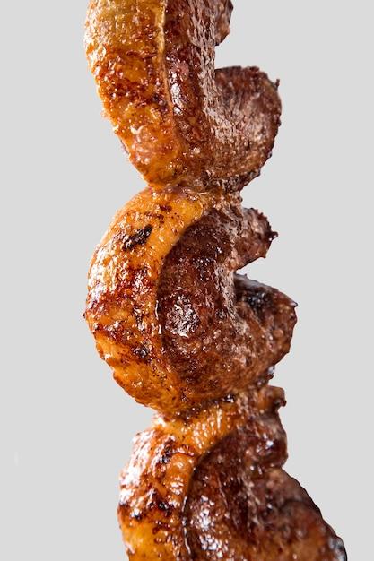 Жаркое на вертеле на белом фоне. пиканья барбекю. Premium Фотографии