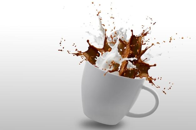 クリッピングパスで白に分離された白いカップのコーヒーと牛乳のスプラッシュ Premium写真