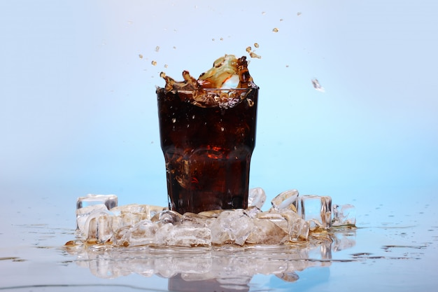 Splashes of cold cola drink Free Photo