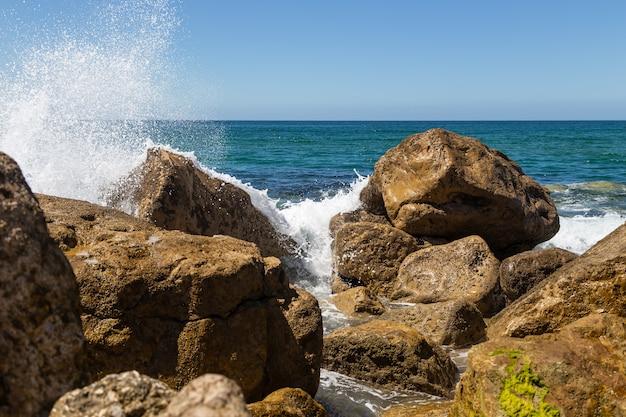 晴れた日の岩の上の波からの水しぶき Premium写真
