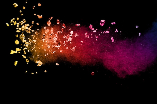 Split debris of colored stone with dust exploding on black Premium Photo