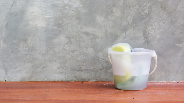 Sponge in the pail prepares for clean a balcony. Premium Photo