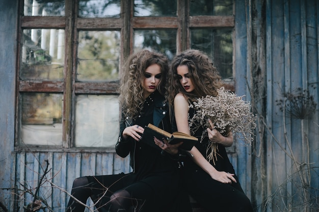 Spooky girls reading a spell Free Photo
