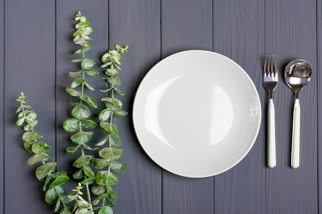 Spoon, fork, grey plate and sprig of green eucalyptus on gray wooden table Premium Photo