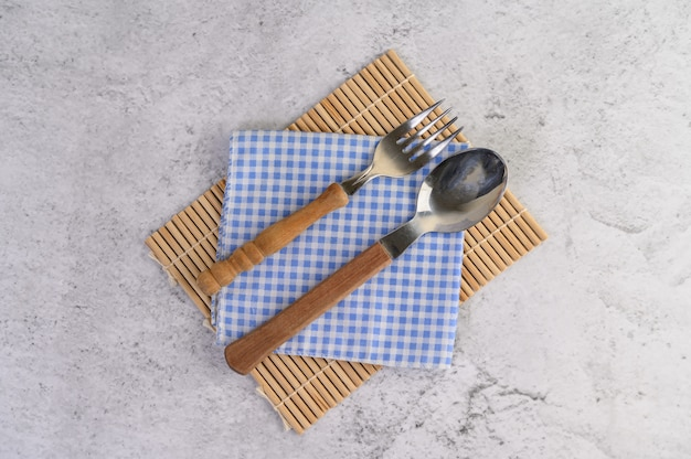 Spoon and fork placed on blue and white handkerchiefs Free Photo