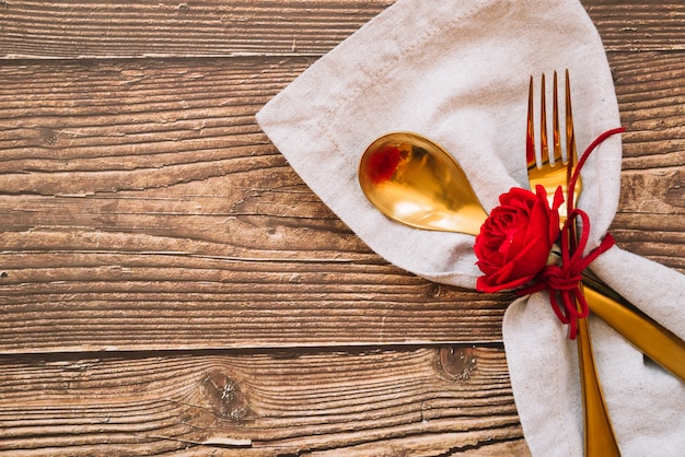 Spoon and fork with red flower on napkin Free Photo
