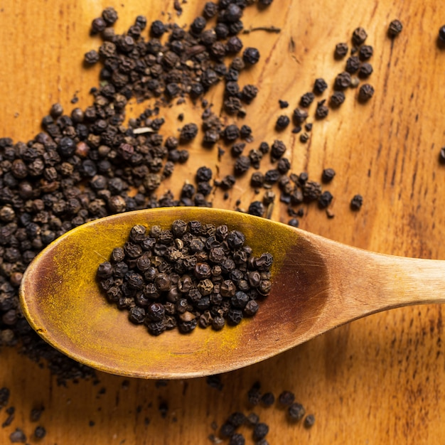 Spoon and heap of pepper on the table Free Photo
