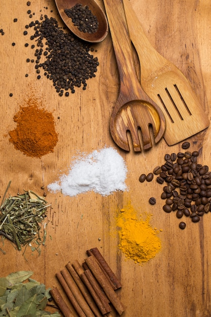 Spoon and heap of spices on the table Free Photo
