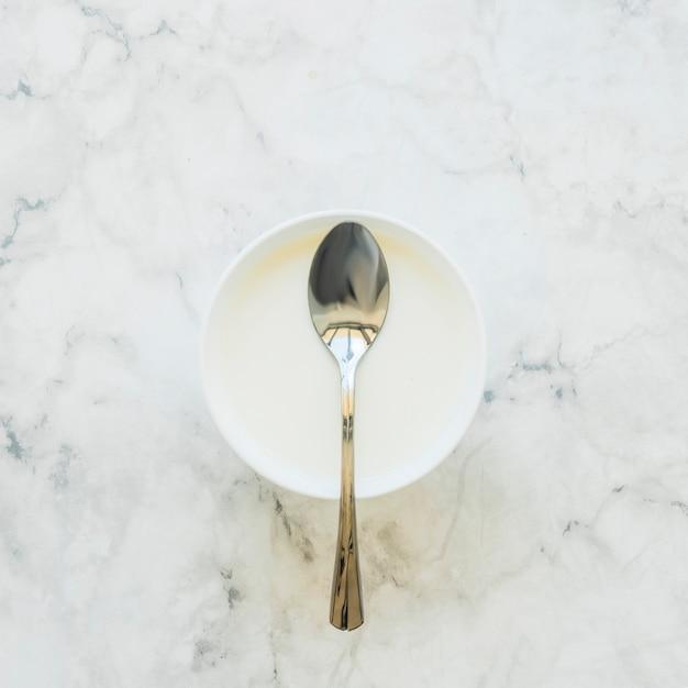 Spoon on white bowl on table Free Photo