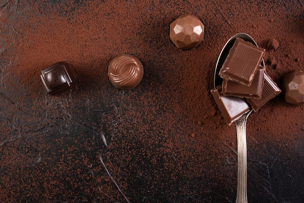 Spoon with chocolate bar squares and candies Free Photo