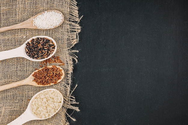 Spoons with assorted rice on linen fabric Free Photo