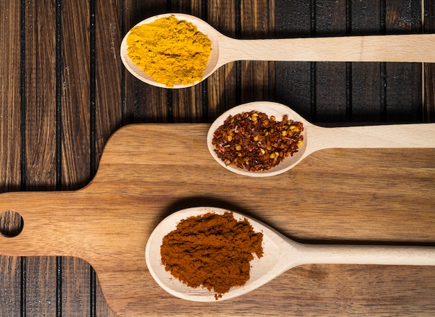 Spoons with hot spices near cutting board Free Photo