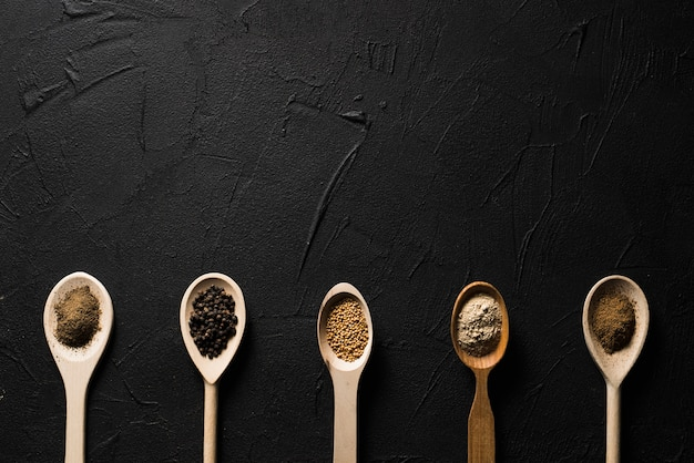 Spoons with spices on black Free Photo