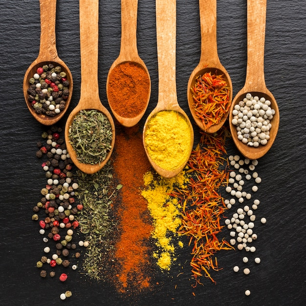 Spoons with spices powder and spread on table Free Photo