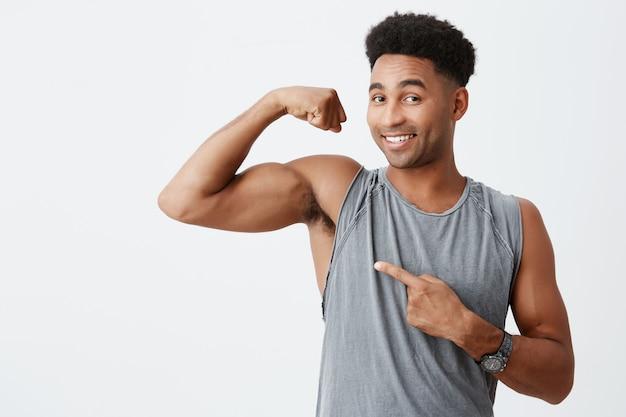 スポーツとライフスタイルのコンセプトです。筋肉を示す巻き毛を持つ暗い肌のハンサムな男。幸せな表情でスポットキャリアについての記事にポーズをとってプロスポーツマン 無料写真
