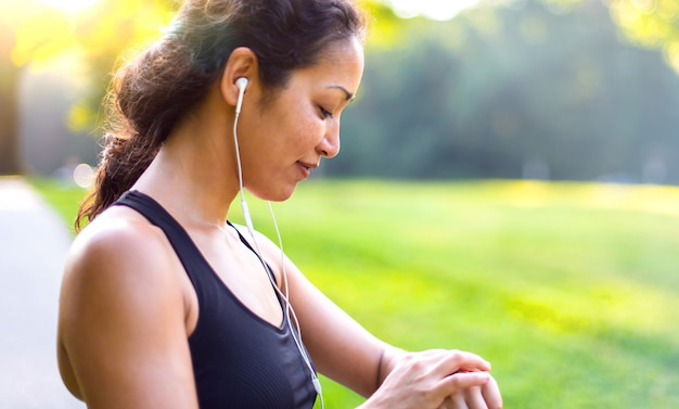 Sport asian woman listening to music with headphones while looking at watch outdoors Premium Photo