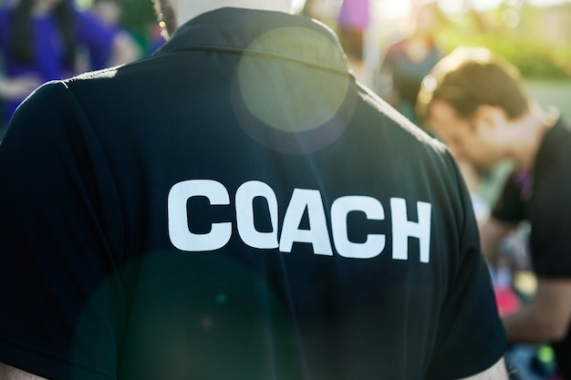 Sport coach in black shirt with white coach text on the back standing outdoor at a school Premium Photo