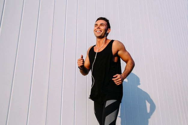 Sport concept smiling handsome muscular guy running outdoors against the white wall 8353 6849