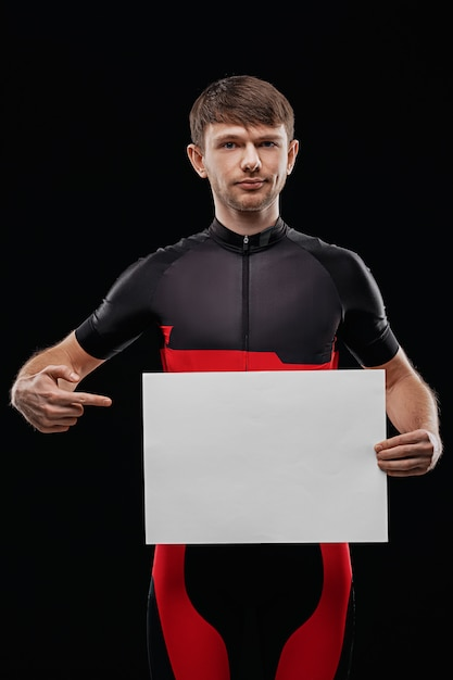 Sport. cyclist in training clothes on black background holding blank sheet of paper. your text here. Premium Photo