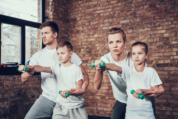 Sport family doing exercises with dumbbells. Premium Photo