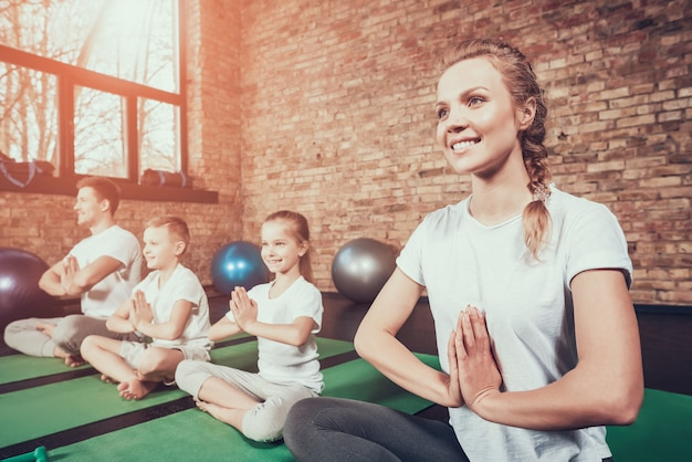 Sport family have yoga training in fitness club. Premium Photo