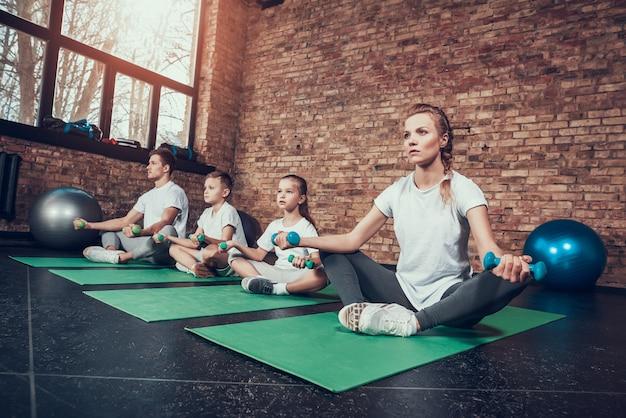 스포츠 가족 휘트니스 클럽에서 체육관 카펫에 앉아. 프리미엄 사진